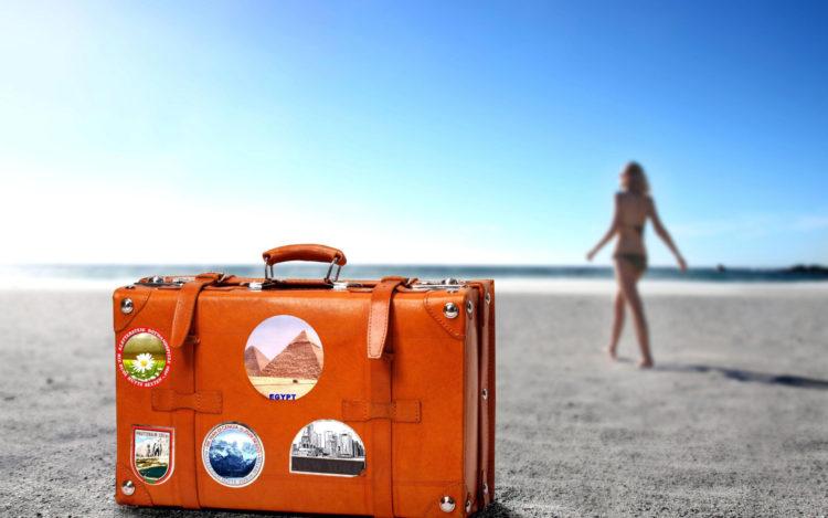 Viagem com idoso - uma mala na praia com uma mulher ao fundo