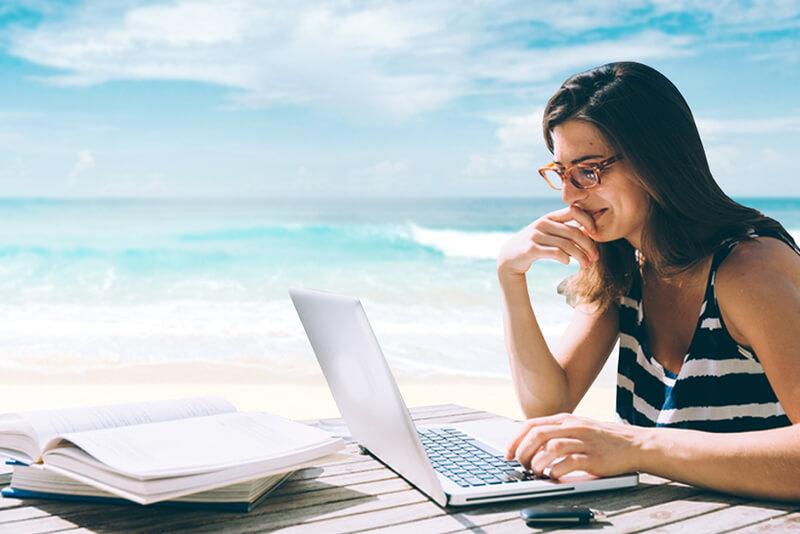 Nômade digital - Mulher usando notebook na praia
